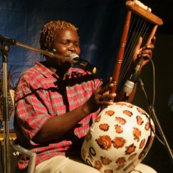 Olith Ratego playing his self-made lyre, the Kodo Madanda